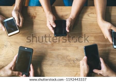 Group of friends playing app games in mobile phone and online together. Hands are holding smartphone circle on the table.