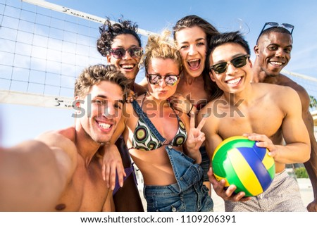 Group of friends playing beach volley and taking a selfie as summer vacation memories