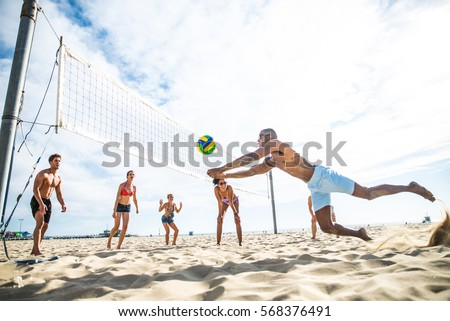 Group of friends playing beach volley - Multi-ethic group of people having fun on the beach #568376491