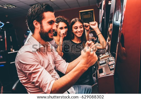 Group of friends playing slot machines - Shutterstock ID 629088302