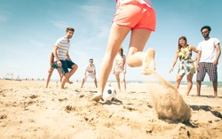 group of friends playing soccer on the beach. a girl is shooting to score a goal. concept about friends, sport, vacations and people