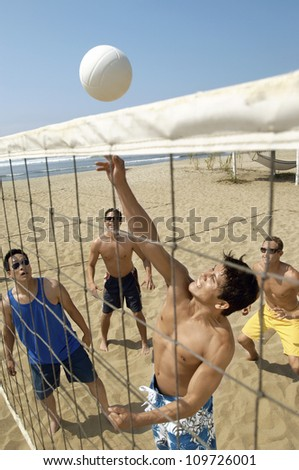 Group of friends playing volleybaLl on the beach
