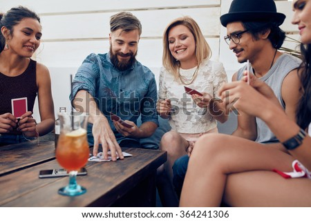 Group of friends relaxing and playing cards together. Young people hanging out together around a table during a party playing a game of cards.