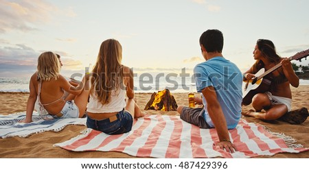 Group of friends relaxing around bonfire on the beach at sunset