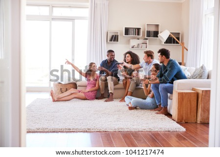 Group Of Friends Relaxing At Home Watching TV Together #1041217474
