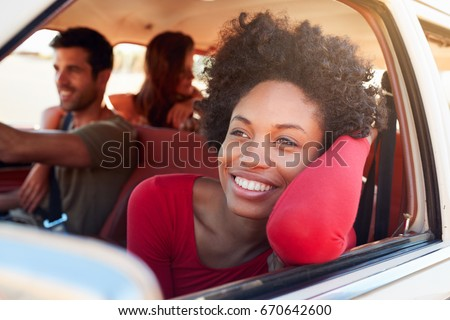 Group Of Friends Relaxing In Car During Road Trip