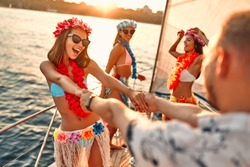 Group of friends relaxing on luxury yacht. Having fun together and dancing on Hawaiian party while sailing in the sea. Traveling and yachting concept.