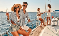 Group of friends relaxing on luxury yacht. Having fun together while sailing in the sea. Traveling and yachting concept.