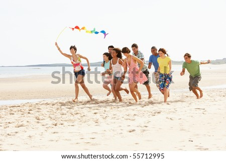Group Of Friends Running Along Beach Together - stock photo