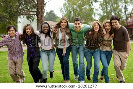 Group of friends running towards the camera outdoors - stock photo