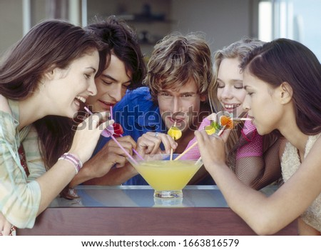 Group of friends sharing a large cocktail