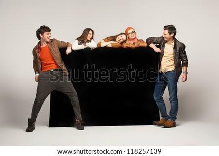 Group of friends showing empty black board
