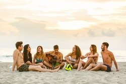 Group of friends singing on the beach. Multicultural group of teenagers and young adult people having fun at seaside. They are talking and playing guitars together. Summer and vacations concepts
