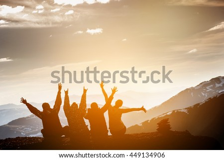 Group of friends sits on the top of mountain and having fun on mountains backdrop  #449134906