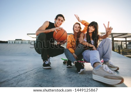 Group of friends sitting at skate park with skateboard and basketball. Male and female friends posing for a portrait at skate park.