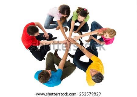 Group Of Friends Sitting In A Circle Stacking Hands Over White Background