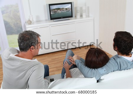 Group of friends sitting in sofa watching tv