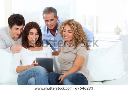 Group of friends sitting in sofa with electronic tab