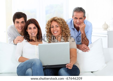 Group of friends sitting in sofa with laptop computer