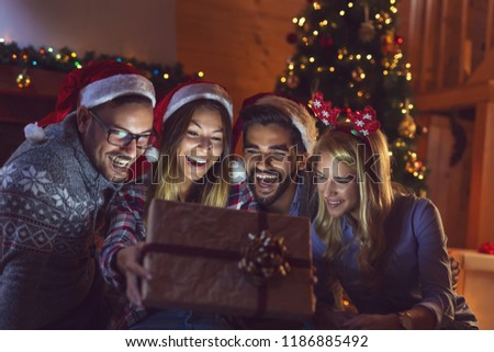 Group of friends sitting next to a fireplace and a nicely decorated Christmas tree, opening presents and having fun on Christmas Eve