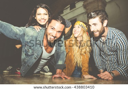 Group of friends sitting on the stairs and taking selfie. Having fun in the night outdoor #438803410