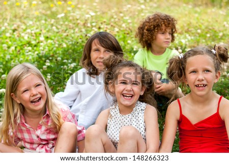 Group of friends sitting together in flower bed.