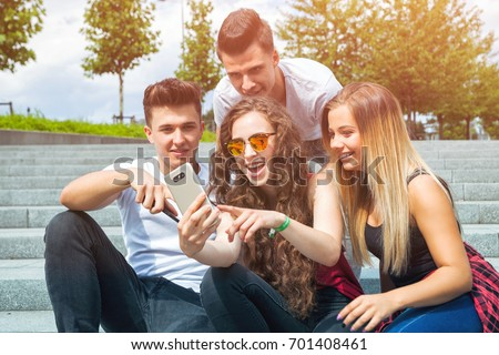 Group of friends sitting together using mobile phone and laughing #701408461