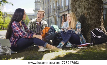 Group of friends sitting under tree talking to each other laughing, togetherness