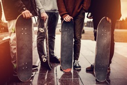 Group of friends skateboarders rest on the street and skateboard, shoes in holes and scuffs. Concept street hooligans. Monochrome and high contrast.