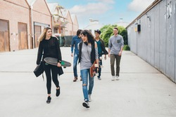 Group of friends skaters walking outdoors having fun chatting and enjoying time together carefree and happy