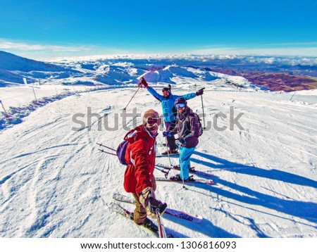 Group of friends skiing on winter holidays at the mountains having fun on the snow