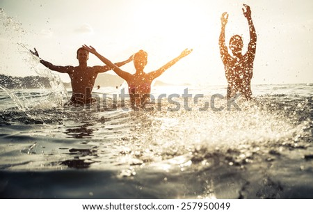 group of friends splashing water in the sea at patong beach, phuket. concept about people and fun