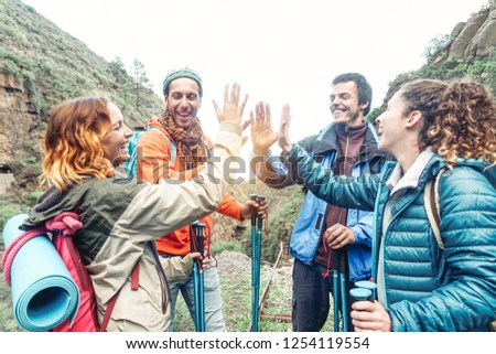 Group of friends stacking hands while doing trekking excursion on mountain - Young tourists walking and exploring the wild nature - Trekker, team, hike and travel people concept
