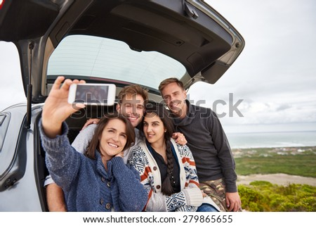 Group of friends taking a roadtrip along the coast posing for selfie at the back of their car