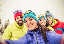 Group of friends taking a selfie - Four snowboarders taking a self portrait with mobile phone - Tourists having fun while skiing - Concepts about winter,christmas,winter vacation and skiing