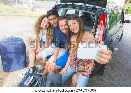 Group of friends taking a selfie in the back of the car before leaving for vacations. They are a mixed race group of four persons, two caucasian and two hispanic.
