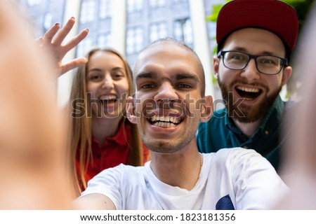 Group of friends taking a stroll on city's street in summer day. Handicapped man with his friends having fun. Inclusion and diversity concept, normal lifestyle of special groups of society.