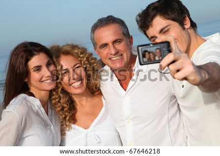 Group of friends taking picture of themselves at the beach