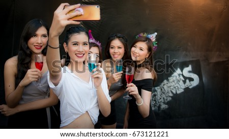 Group of friends taking selfie at party,Party, holidays,Technology, Nightlife and people concept - smiling friends with glasses of champagne and smartphone taking self-ie in club, Age 20-30 years. #673121221