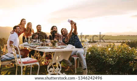 Group of friends taking selfie on a smart phone at dinner party. Young people on dinner party in garden taking selfie.