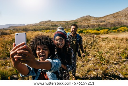 Group of friends taking selfie on country hike. Young people hiking in countryside and taking pictures with smart phone.
