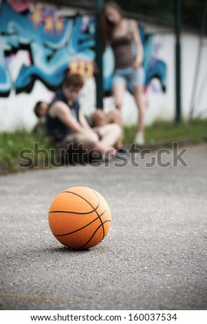 Group of friends talking and taking a break after playing basketball, focus on ball