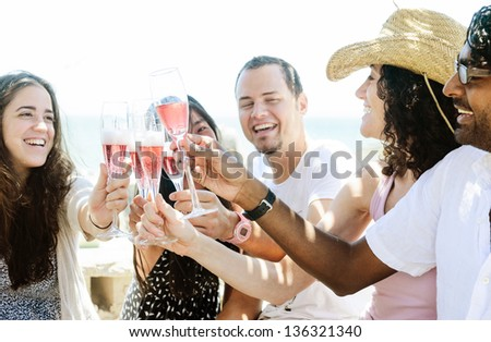 Group of friends toasting champagne sparkling wine at a relax party celebration gathering by the sunny beach