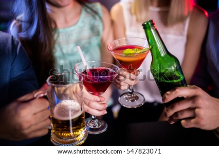 Group of friends toasting cocktail, beer bottle and beer glass at bar counter in bar