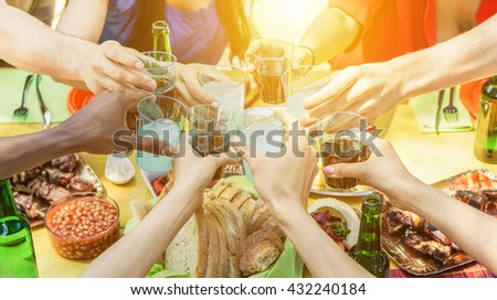 Group of friends toasting with aperitif eating barbecue outdoor - Closeup of hands cheering with cocktails and beers - Friendship,summer,fun and dinner concept - Warm filtered look