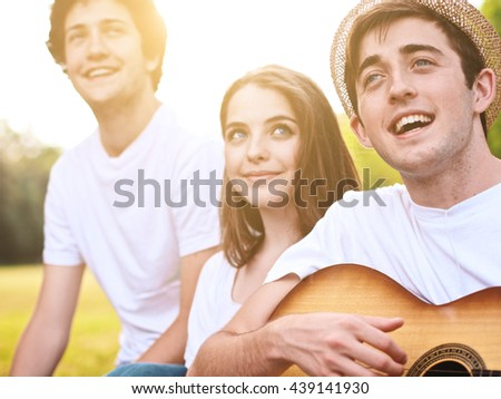 group of friends together in a park having fun and playing music with a guitar #439141930