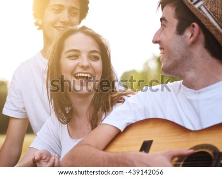 group of friends together in a park having fun and playing music with a guitar #439142056