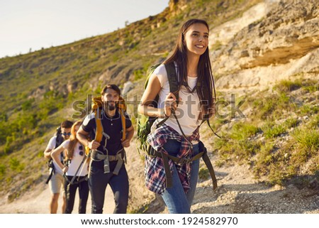 Group of friends tourists with backpacks traveler in the mountains on a hike hiking along the route in nature in summer. Outdoor activities adventure for people.