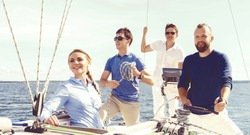 Group of friends traveling on a yacht and enjoying a good summer day. Vacation, holiday, summertime concept.
