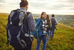 Group of friends trekking with backpacks walking in the forest .